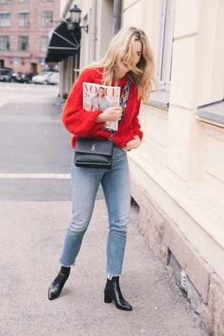 Cómo combinar: jersey oversized de punto rojo, vaqueros pitillo celestes, botines de cuero negros, bolso bandolera de cuero negro