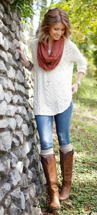 Cómo combinar: jersey oversized de punto blanco, vaqueros azules, botas de caña alta de cuero marrónes, calcetines hasta la rodilla en beige