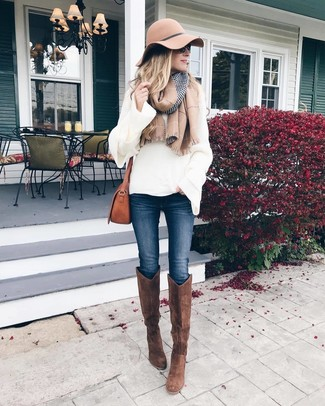 Cómo combinar: jersey oversized de punto blanco, vaqueros pitillo azul marino, botas de caña alta de ante marrónes, bolso bandolera de cuero marrón