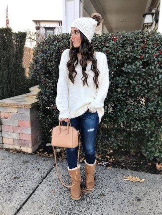 Cómo combinar: jersey oversized de punto blanco, vaqueros pitillo desgastados azul marino, botas ugg marrón claro, bolsa tote de cuero rosada