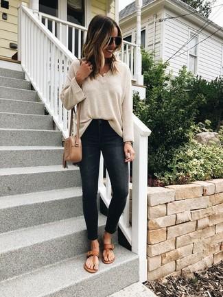 Cómo combinar: jersey oversized en beige, vaqueros pitillo negros, sandalias de dedo de cuero marrónes, bolso bandolera de cuero marrón claro