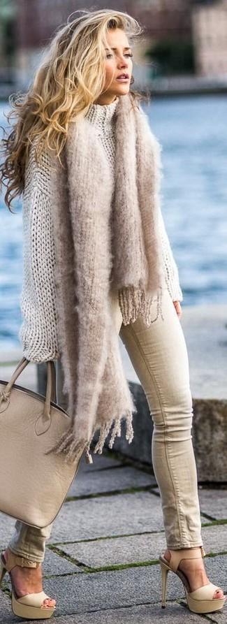 Cómo combinar: jersey oversized de punto en beige, vaqueros pitillo en beige, sandalias de tacón de cuero en beige, bolsa tote de cuero marrón claro