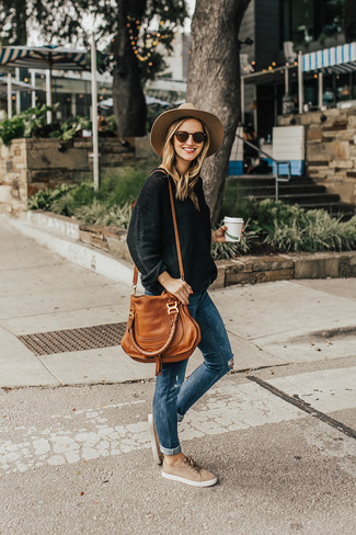 Cómo combinar: jersey oversized negro, vaqueros pitillo desgastados azules, tenis de ante en beige, bolsa tote de cuero en tabaco