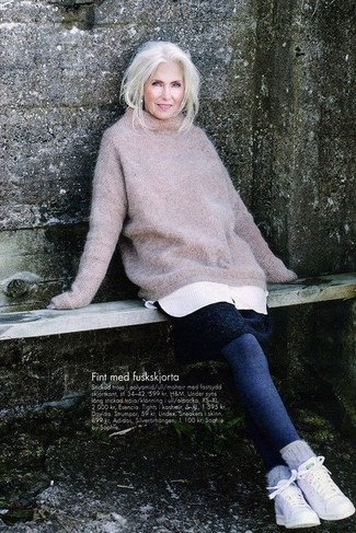 Moda para mujeres de 60 años: Para un atuendo tan cómodo como tu sillón elige un jersey oversized de punto en beige y unos leggings azul marino. ¿Te sientes valiente? Usa un par de tenis blancos.