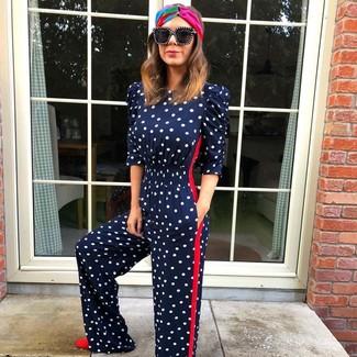 Cómo combinar: mono a lunares azul marino, zapatos de tacón de ante rojos, gafas de sol negras, cinta para la cabeza en multicolor