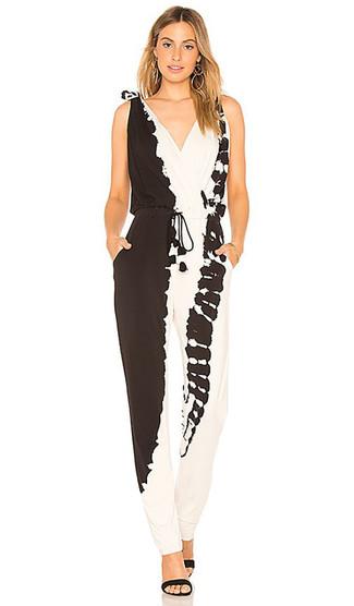 Cómo combinar: mono efecto teñido anudado en negro y blanco, sandalias de tacón de ante negras, pendientes dorados