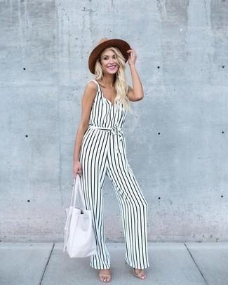 Cómo combinar: mono de rayas verticales en blanco y negro, sandalias de tacón de cuero en beige, bolsa tote de cuero blanca, sombrero de paja marrón