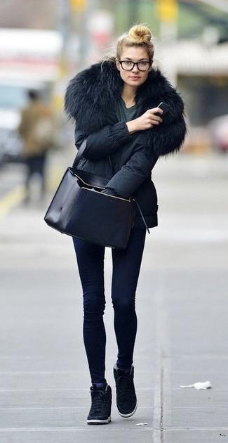 Cómo combinar: parka negra, camiseta con cuello circular en gris oscuro, vaqueros pitillo azul marino, zapatillas con cuña de ante negras