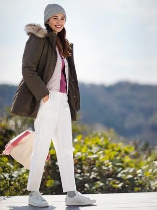 Una parka verde oliva y un pantalón chino blanco son una opción muy buena para el fin de semana. Este atuendo se complementa perfectamente con tenis de cuero blancos.