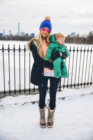 Para seguir las tendencias usa una parka negra y unos vaqueros pitillo negros. ¿Por qué no añadir botas para la nieve grises a la combinación para dar una sensación más relajada?