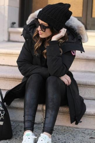 Cómo combinar: parka negra, leggings de cuero negros, tenis de cuero blancos, bolsa tote de cuero negra