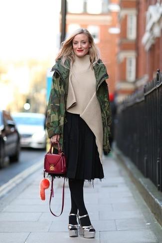Cómo combinar: parka de camuflaje verde oscuro, poncho en beige, falda midi plisada negra, sandalias de tacón de cuero gruesas plateadas