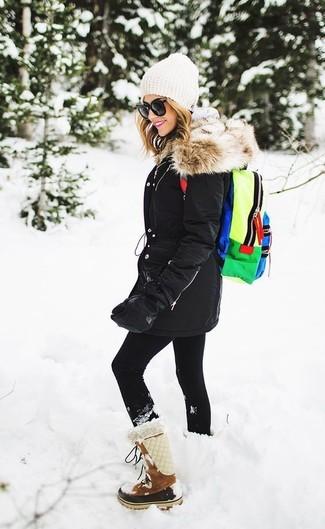 Emparejar una parka negra junto a unos leggings negros es una opción inmejorable para el fin de semana. Completa el look con botas para la nieve de ante marrónes.