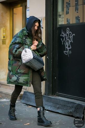 Cómo combinar: parka de camuflaje verde oscuro, sudadera con capucha negra, vaqueros pitillo estampados verde oliva, botas planas con cordones de cuero negras
