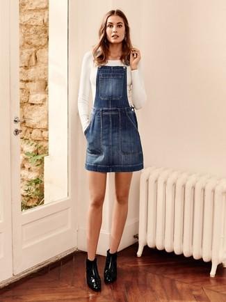 Si eres el tipo de chica de jeans y camiseta, te va a gustar la combinación de una camiseta de manga larga blanca de Inside y un pichi vaquero azul marino. Botines de cuero negros levantan al instante cualquier look simple.