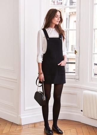 Emparejar un pichi negro y una blusa de manga larga blanca es una opción cómoda para hacer diligencias en la ciudad. Mocasín son una forma sencilla de mejorar tu look.