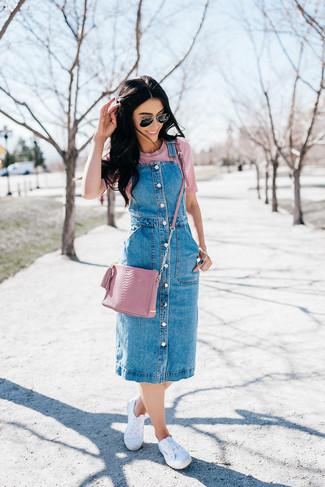 Si eres el tipo de chica de jeans y camiseta, te va a gustar la combinación de un pichi vaquero azul y una camiseta con cuello circular rosada. Tenis de lona blancos son una opción perfecta para completar este atuendo.