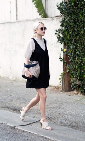Cómo combinar una camiseta con cuello en v blanca: Una camiseta con cuello en v blanca y un pichi negro son una opción grandiosa para el fin de semana. Elige un par de sandalias con cuña de cuero blancas para mostrar tu lado fashionista.