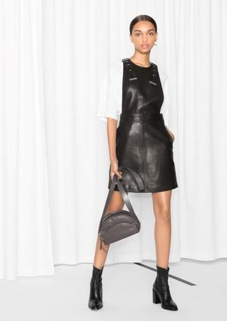 Cómo combinar: pichi de cuero negro, blusa de manga corta blanca, botines de cuero negros, riñonera de cuero en gris oscuro