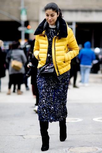 Cómo combinar: plumífero amarillo, vestido midi estampado azul marino, botas de caña alta de ante negras, bolso bandolera de cuero con adornos negro
