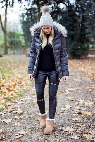 Un plumífero gris oscuro y unos vaqueros pitillo de cuero negros son el combo perfecto para llamar la atención por una buena razón. Si no quieres vestir totalmente formal, opta por un par de botas ugg beige.