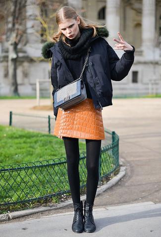 Cómo combinar: plumífero negro, jersey con cuello vuelto holgado negro, minifalda de cuero naranja, botas planas con cordones de cuero negras