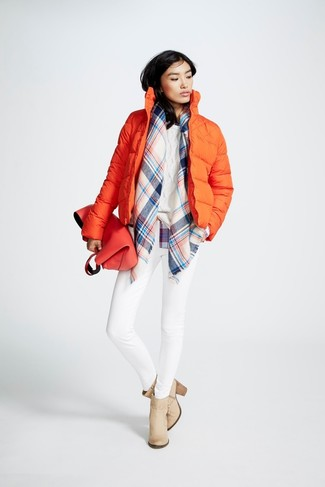 Cómo combinar: plumífero naranja, jersey de ochos blanco, vaqueros pitillo blancos, botines de cuero en beige