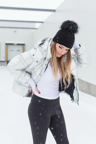 Cómo combinar: plumífero plateado, jersey de cuello alto blanco, leggings negros, gorro negro