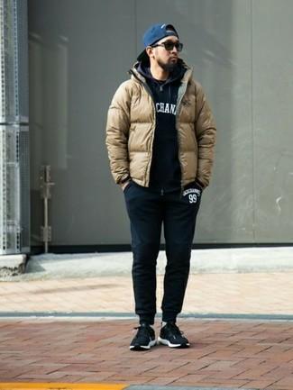 Cómo combinar: plumífero marrón claro, sudadera con capucha estampada en negro y blanco, camiseta con cuello circular negra, pantalón de chándal negro