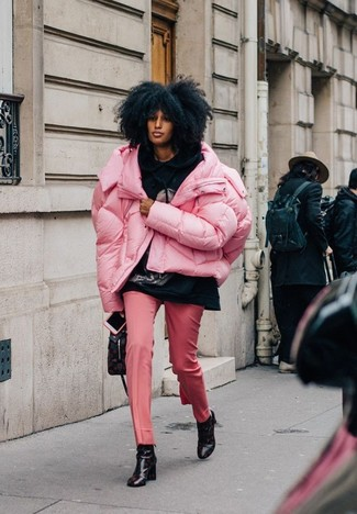 Cómo combinar: plumífero rosado, sudadera con capucha estampada negra, pantalón de vestir rosado, botines de cuero estampados negros
