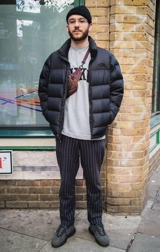 Cómo combinar un plumífero negro: Empareja un plumífero negro junto a un pantalón chino de rayas verticales azul marino para el after office. ¿Te sientes valiente? Completa tu atuendo con deportivas en gris oscuro.