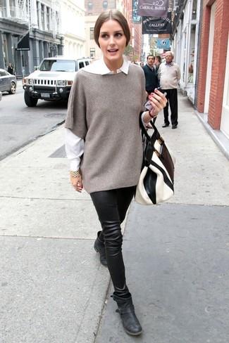 Cómo combinar: poncho gris, camisa de vestir blanca, leggings de cuero negros, botines de cuero negros