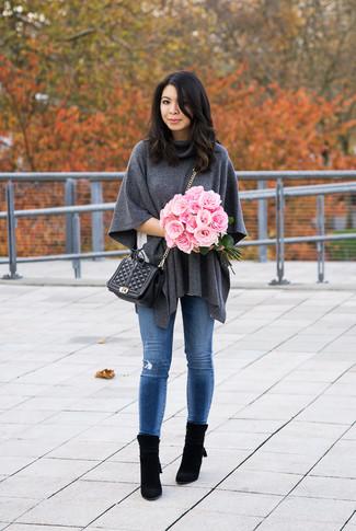 Cómo combinar: poncho de lana en gris oscuro, camiseta con cuello circular blanca, vaqueros pitillo desgastados azules, botines de ante negros
