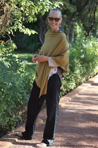 Cómo combinar: poncho verde oliva, camiseta de manga larga estampada blanca, pantalones anchos negros, sandalias planas de cuero en beige
