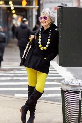 Cómo combinar: poncho negro, camiseta de manga larga amarilla, pantalones pitillo amarillos, botas sobre la rodilla de ante negras