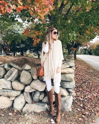 Cómo combinar unas botas de caña alta de ante marrónes: Empareja un poncho de punto en beige con unos vaqueros pitillo blancos para una apariencia fácil de vestir para todos los días. Elige un par de botas de caña alta de ante marrónes para destacar tu lado más sensual.