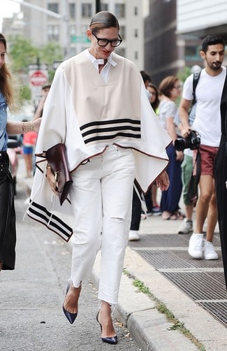 Look de Jenna Lyons: Poncho de Rayas Horizontales en Beige, Vaqueros Desgastados Blancos, Zapatos de Tacón de Cuero Azul Marino, Cartera Sobre de Cuero Burdeos