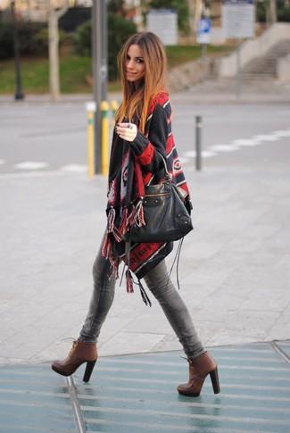 Cómo combinar: poncho estampado negro, vaqueros pitillo grises, botines con cordones de cuero marrónes, bolsa tote de cuero negra
