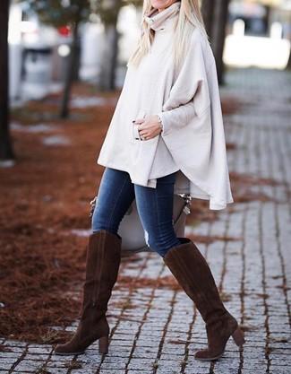Cómo combinar: poncho en beige, vaqueros pitillo azules, botas de caña alta de ante en marrón oscuro, bolsa tote de cuero en beige