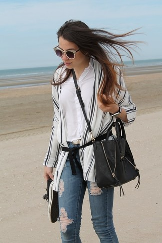 Cómo combinar: quimono de rayas verticales en blanco y negro, camisa de vestir blanca, vaqueros pitillo desgastados azules, tenis negros