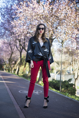 Cómo combinar: quimono estampado negro, camiseta sin manga en beige, pantalones pitillo rojos, zapatos de tacón de ante negros
