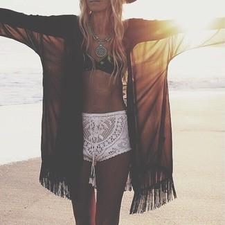 Cómo combinar: quimono de gasa negro, top de bikini de crochet negro, pantalones cortos de crochet blancos, collar plateado