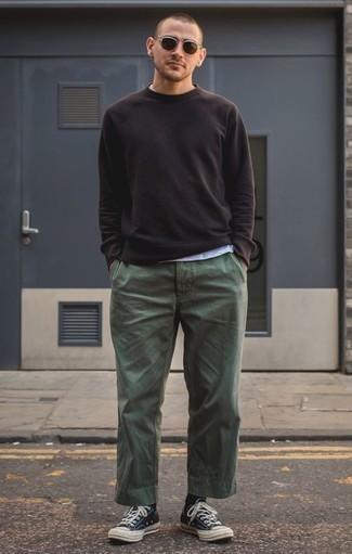 Cómo combinar un pantalón chino verde oscuro: Para crear una apariencia para un almuerzo con amigos en el fin de semana equípate una sudadera negra junto a un pantalón chino verde oscuro. Tenis de lona en negro y blanco son una opción buena para completar este atuendo.