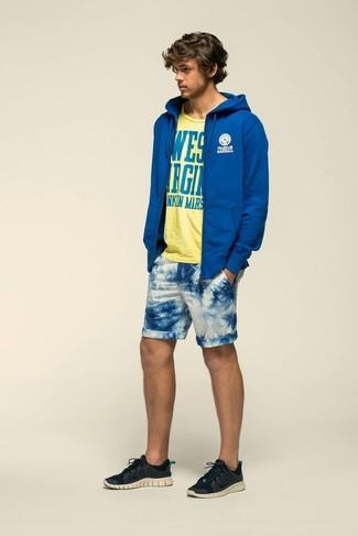 Cómo combinar: sudadera con capucha azul, camiseta con cuello circular estampada amarilla, pantalones cortos estampados en blanco y azul, deportivas negras