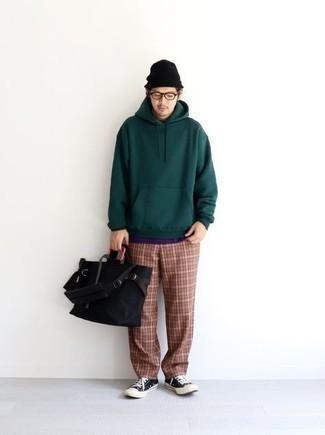 Cómo combinar una bolsa tote de lona negra: Emparejar una sudadera con capucha verde oscuro con una bolsa tote de lona negra es una opción perfecta para el fin de semana. ¿Te sientes valiente? Haz tenis de lona en negro y blanco tu calzado.