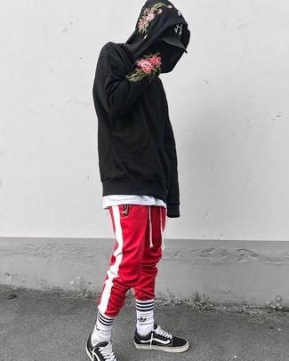 Cómo combinar: sudadera con capucha con print de flores negra, camiseta con cuello circular blanca, pantalón de chándal de rayas verticales en rojo y blanco, tenis de lona en negro y blanco