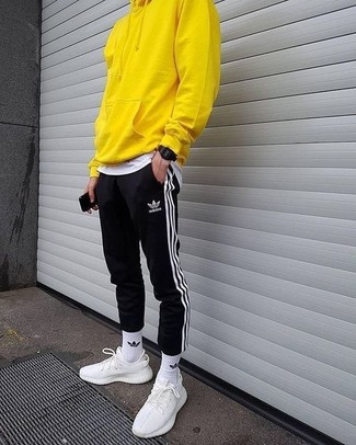 Cómo combinar: sudadera con capucha amarilla, camiseta con cuello circular blanca, pantalón de chándal de rayas verticales en negro y blanco, deportivas blancas
