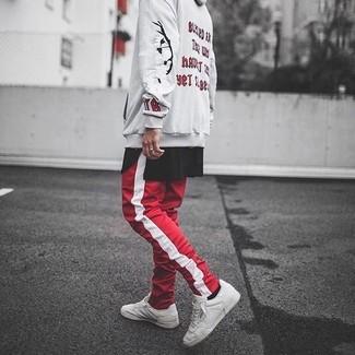 Cómo combinar: sudadera con capucha estampada en beige, camiseta con cuello circular negra, pantalón de chándal de rayas verticales en rojo y blanco, tenis de cuero blancos