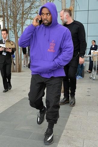 Una sudadera con capucha en violeta y un pantalón de chándal negro son tu atuendo para salir los días de descanso. Un par de deportivas negras se integra perfectamente con diversos looks.