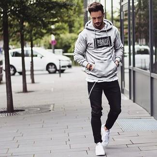 Cómo combinar: sudadera con capucha estampada gris, pantalón chino negro, tenis blancos